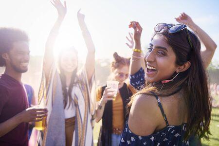 Glückliche Asiatin und ihre Freunde beim Musikfestival