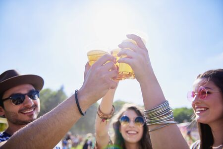 Friends drinking beer and having fun in festival