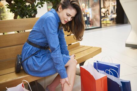 Woman suffering from leg pain during shopping