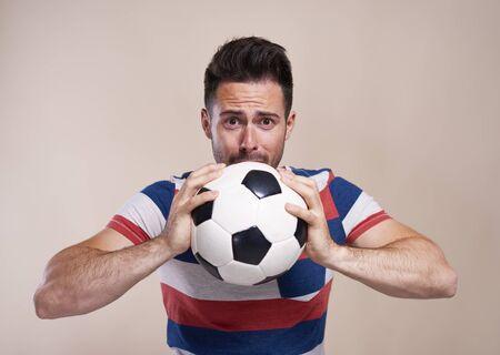 Nervous soccer fan with soccer ball
