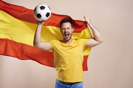 Screaming Spanish fan holding flag and soccer ball