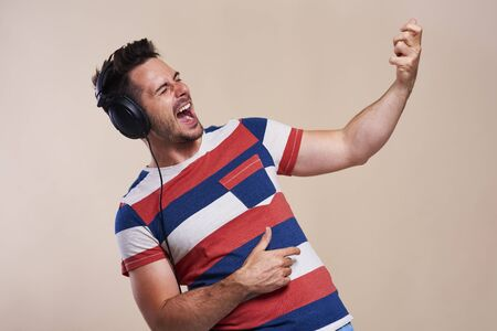 Playful man listening to music and playing air guitar