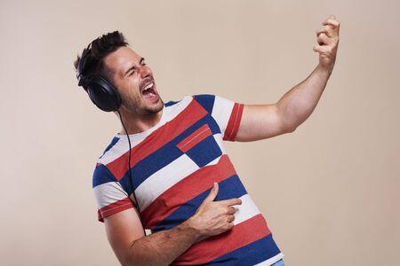 Uomo allegro che ascolta musica e suona la chitarra ad aria