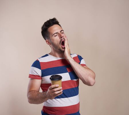 Tired man yawning and holding disposable cup of coffee