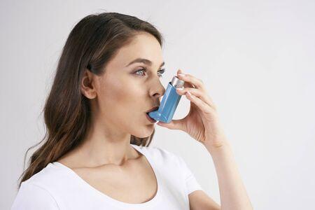 Mujer asmática que usa un inhalador para el asma durante los ataques de asma Foto de archivo