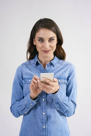 Portrait of smiling woman holding mobile phone in studio shot