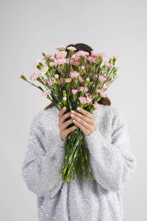 Woman holding bunch of flowers in front of her face