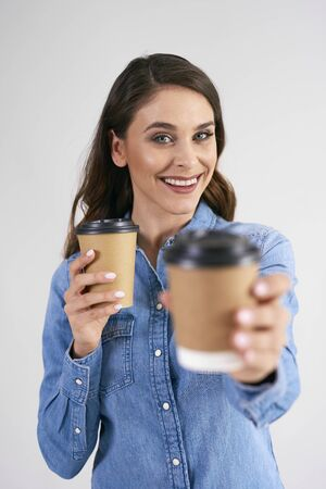 Portrait of smiling woman holding disposable cup of coffee