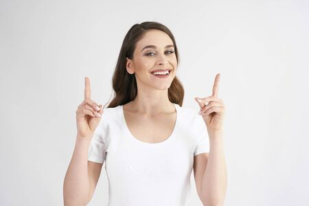 Smiling woman pointing at copy space