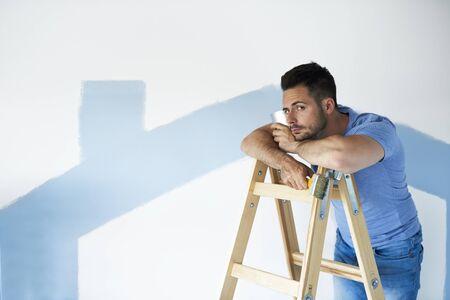 Porträt eines gelangweilten und unzufriedenen Mannes, der eine Pause vom Malen einlegt Standard-Bild