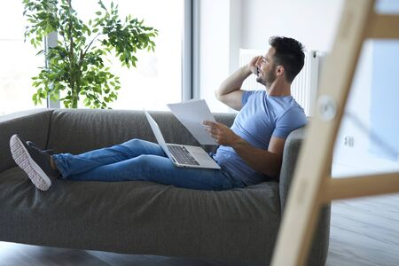 Young man working with technology in living room