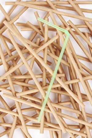 Plastic straw among drinking straw made from bamboo