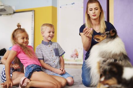 Happy kids with dog during therapy