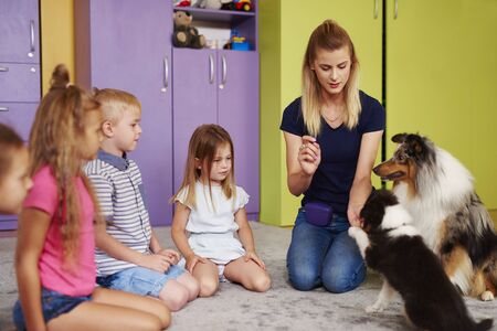 Small group of children playing with therapy dog in the preschool