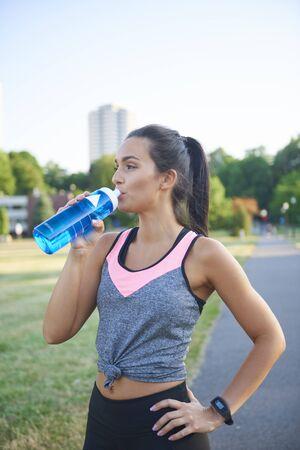 Junge Frau trinkt Wasser nach hartem Training