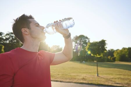 Tired man drinking water after workout Stock fotó