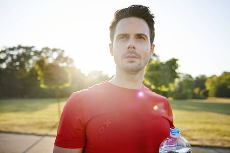 Young man drinking water after hard workout