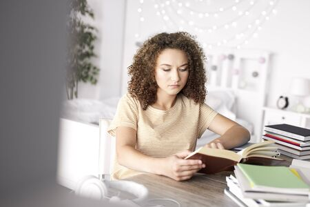 Focused teenage girl reading a book in her room Stock Photo