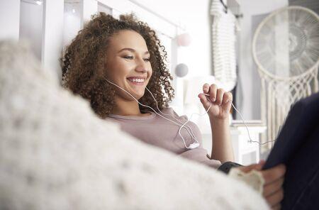 Smiling teenage girl listening to music in her room