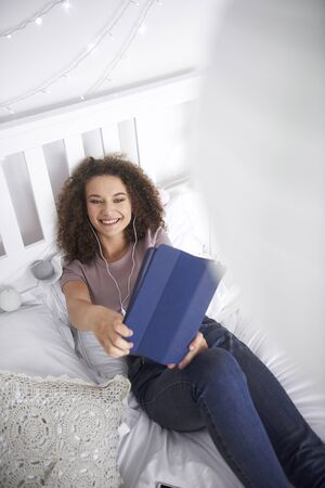 Smiling teenage girl making a selfie in her bed