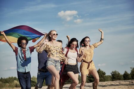 Happy friends with rainbow flag running outdoors Stock Photo
