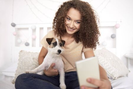Teenage girl and her dog making a selfie