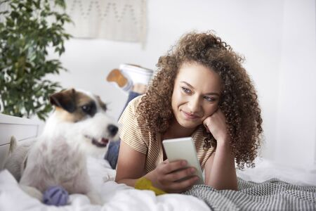 Young woman lying on the bed and using mobile phone