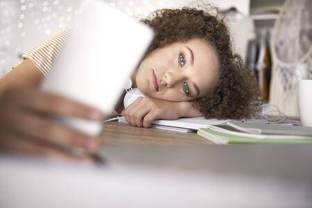 Worried teenage girl lying on books at desk Фото со стока