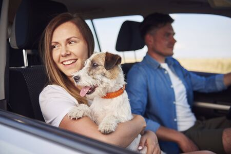 Young couple and their dog traveling together in a car