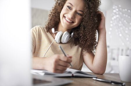 Smiling teenage girl studying at home