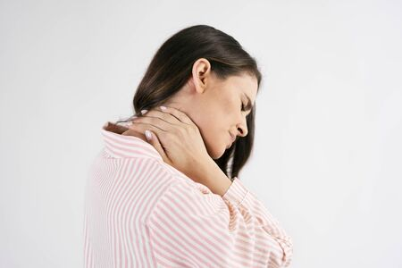 Side view of young woman suffering from neck pain