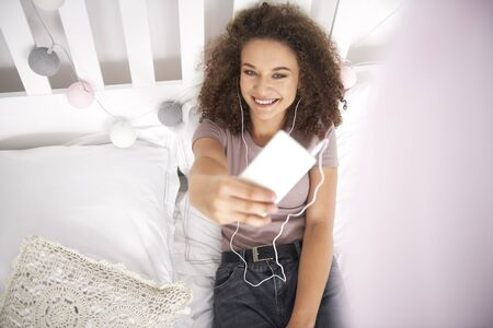 Smiling teenage girl making a selfie on the bed Stock Photo
