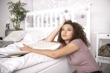 Worried teenage girl thinking about something in the bedroom