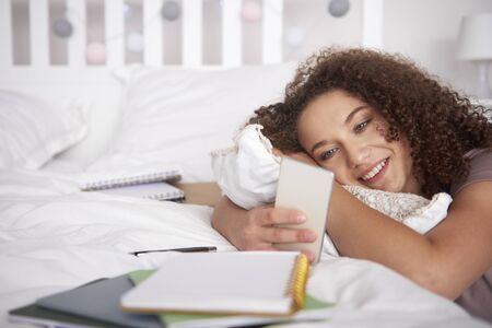 Smiling teenage girl using a smart phone in her room Stock Photo