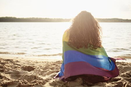 Rear view of young woman covered with rainbow flag