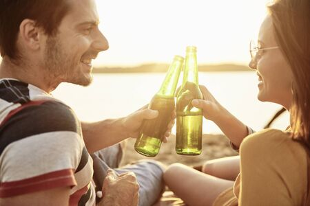 Young couple drinking beer on the beach