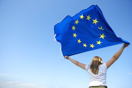 Rear view of young woman waving the European Union flag