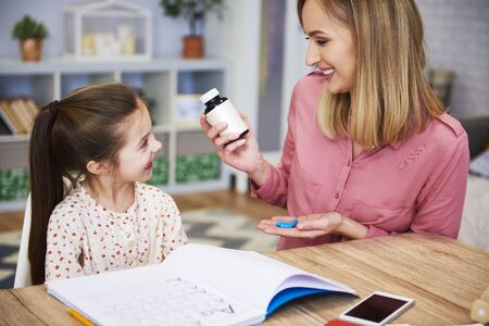 Young mother giving pills to her daughter while doing homework