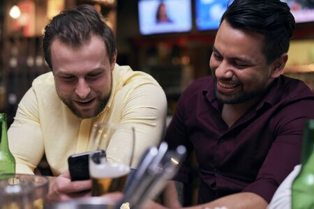 Men using mobile phone at the bar Reklamní fotografie