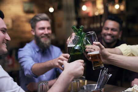 Group of men making a cheers for good weekend