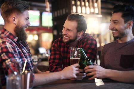 Three smiling men drinking beer in the pub Reklamní fotografie