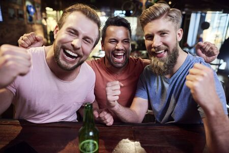 Portrait of three screaming men in the pub Reklamní fotografie