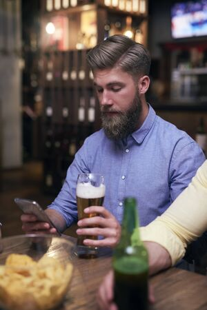 Hipster man using mobile phone and drinking beer Reklamní fotografie
