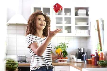 Young woman having fun with pepper in the kitchen