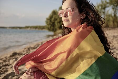 Young woman wrapped in rainbow flag on the beach Reklamní fotografie