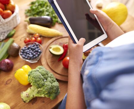 Woman with digital tablet in the kitchen
