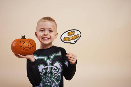 Smiling boy start decorating the pumpkins