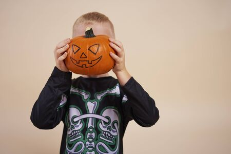 Little boy holding halloween pumpkin in front of his face