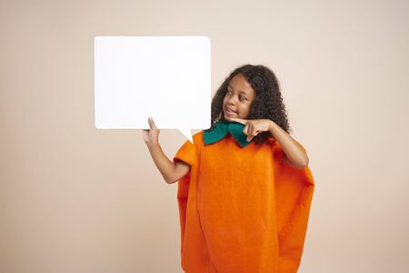 African girl in halloween costume holding empty speech bubble