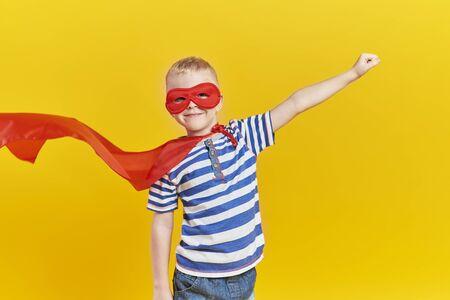 Portrait of playful boy in superhero costume Standard-Bild
